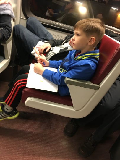 Luke thinking about what to draw next with Parker asleep next to him on the Metro.
